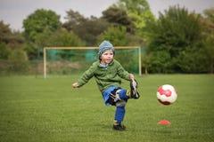 Garçon jouant au football images stock