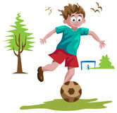 Garçon jouant au football Image stock