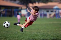 Garçon jouant au football en stationnement Image libre de droits