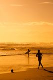 Garçon jouant au football sur la plage Photographie stock