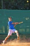 Garçon jouant au tennis heurtant la bille avec le revers Photographie stock libre de droits
