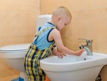 Garçon jouant avec de l'eau Photo stock