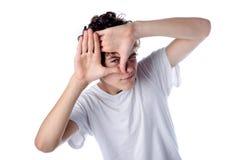 Garçon jouant avec des mains devant son visage Images stock