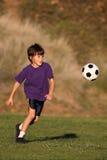 Garçon jouant avec la bille de football Image stock