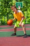 Garçon jouant avec la boule seule pendant le match de basket photographie stock libre de droits