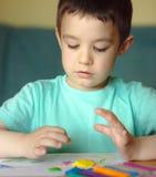 Garçon jouant avec la pâte de jeu de couleur Photo stock