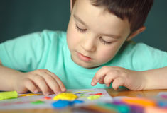 Garçon jouant avec la pâte de jeu de couleur Photographie stock