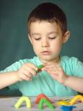 Garçon jouant avec la pâte de jeu de couleur Photos libres de droits