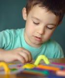 Garçon jouant avec la pâte de jeu de couleur Image stock