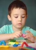Garçon jouant avec la pâte de jeu de couleur Images stock