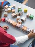 Garçon jouant avec le bloc d'alphabet dans la classe Photographie stock libre de droits
