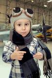 Garçon jouant avec le chapeau de pilotes photo stock
