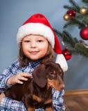 Garçon jouant avec le chien près du sapin de Noël Image stock