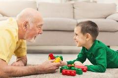 Garçon jouant avec le grand-père dans le kit de bâtiment Image libre de droits