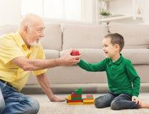 Garçon jouant avec le grand-père dans le kit de bâtiment Images stock