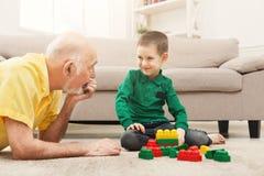 Garçon jouant avec le grand-père dans le kit de bâtiment Photographie stock