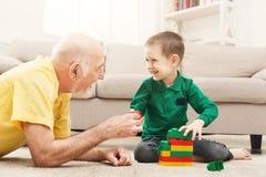 Garçon jouant avec le grand-père dans le kit de bâtiment Images libres de droits