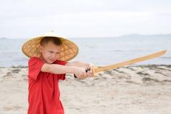 Garçon jouant avec le katana des enfants Photo libre de droits