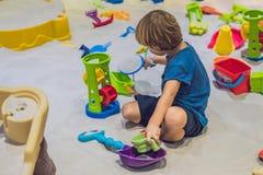 Garçon jouant avec le sable dans l'école maternelle Le développement du concept fin de moteur Concept de jeu de créativité photos libres de droits
