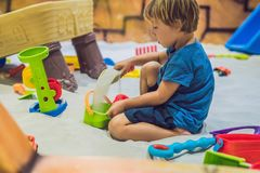 Garçon jouant avec le sable dans l'école maternelle Le développement du concept fin de moteur Concept de jeu de créativité photo stock