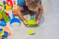 Garçon jouant avec le sable dans l'école maternelle Le développement du concept fin de moteur Concept de jeu de créativité image stock