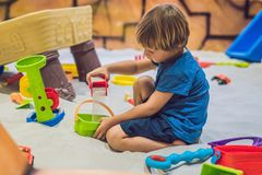 Garçon jouant avec le sable dans l'école maternelle Le développement du concept fin de moteur Concept de jeu de créativité images stock