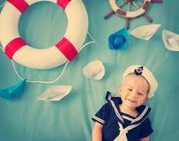 Garçon jouant avec les bateaux de papier Images stock
