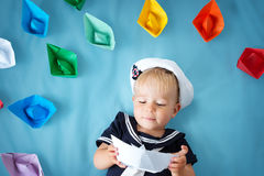 Garçon jouant avec les bateaux de papier Photo stock
