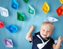 Garçon jouant avec les bateaux de papier Photographie stock libre de droits