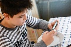 Garçon jouant avec son téléphone pendant le déjeuner photographie stock libre de droits