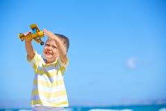Garçon jouant avec un avion de jouet Photos stock