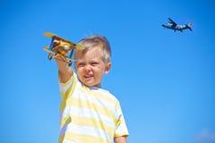 Garçon jouant avec un avion de jouet Photos libres de droits