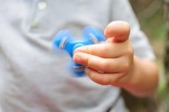 Garçon jouant avec un tri fileur de main de personne remuante Images libres de droits
