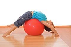 Garçon jouant avec une bille gymnastique photo stock