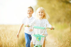 Garçon jouant avec une fille dans le domaine d'automne Photo libre de droits