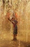 Garçon jouant dans la fontaine. Images stock