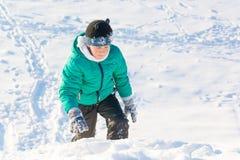 Garçon jouant dans la neige Photos stock
