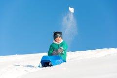 Garçon jouant dans la neige Photo stock