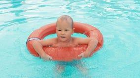 Garçon jouant dans la piscine avec la bouée de sauvetage clips vidéos