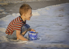 Garçon jouant dans la vague déferlante Photo libre de droits