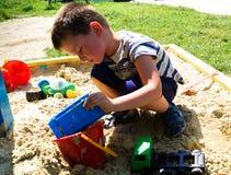 Garçon jouant dans le bac à sable Photographie stock libre de droits