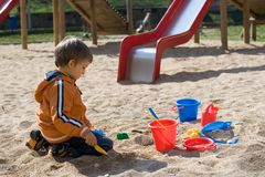 Garçon jouant dans le cadre de sable Photographie stock