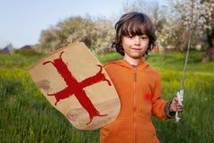 Garçon jouant dans le chevalier médiéval images stock