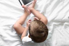 Garçon jouant dans le comprimé images stock