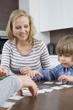 Garçon jouant des cartes avec des parents à la maison Photo libre de droits