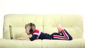Garçon jouant des jeux sur Internet sur l'ordinateur portable dans des écouteurs, mouvement lent banque de vidéos
