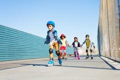 Garçon jouant des patins de rouleau avec des amis dehors Images stock