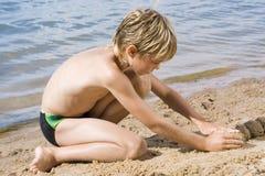 Garçon jouant en sable Images stock