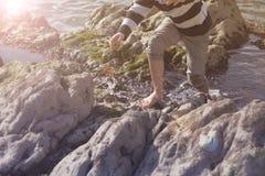 Garçon jouant et explorant dans les piscines de marée près de l'océan Photos libres de droits