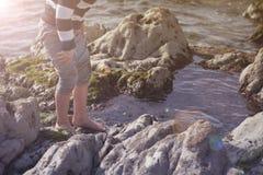 Garçon jouant et explorant dans les piscines de marée près de l'océan Image libre de droits